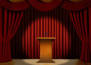 Podium in a spot light on stage over red curtains